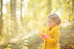 El jugar caucásico del bebé del pequeño niño con la hoja, fondo de Autumn Nature Muchacha de ojos azules rubia linda en amarillo  fotografía de archivo