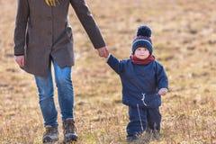 El jugar caucásico feliz del niño al aire libre - caminando con su madre Fotografía de archivo