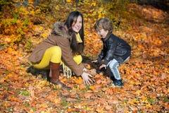 El jugar con las hojas de otoño Foto de archivo libre de regalías