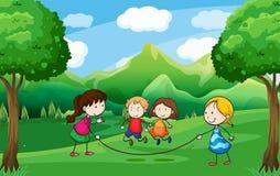 El jugar de cuatro niños al aire libre cerca de los árboles Fotografía de archivo libre de regalías