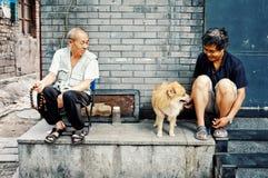 El jugar de dos mangos con un perro fuera de su hogar en un hutong chino tradicional de la ciudad fotografía de archivo libre de regalías