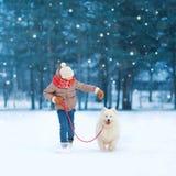 El jugar de funcionamiento del muchacho feliz del adolescente de la Navidad con el perro blanco del samoyedo en nieve en día de i Imágenes de archivo libres de regalías
