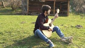 El jugar de la guitarra Hombre que juega música en una guitarra acústica cadenas almacen de metraje de vídeo