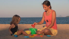 El jugar de la madre y de la hija golpean en el cubo y la risa de la pala almacen de video