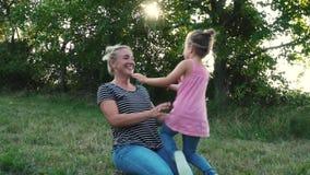 El jugar de la madre y de la hija al aire libre