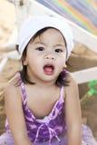 El jugar de la niña y su cara sucios con la arena fotografía de archivo