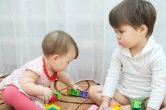 El jugar de las hermanas Dos niñas, bebé y niño niño celoso Imagen de archivo