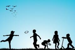 El jugar de las siluetas de los niños al aire libre Fotografía de archivo libre de regalías
