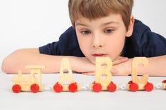 El jugar de mentira del muchacho con el ferrocarril del alfabeto Foto de archivo libre de regalías