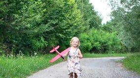 El jugar de niño lindo de la niña con el concepto de oro del juego de la inocencia de la niñez de la hora de Toy In Park At Sunse almacen de video