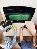 El jugar de niños en la consola de los juegos para jugar a fútbol Imagen de archivo