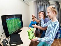 El jugar de niños en la consola de los juegos para jugar a fútbol Imágenes de archivo libres de regalías