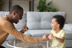 El jugar de risa del padre negro con el pequeño niño en casa imagenes de archivo
