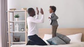 El jugar de salto del hijo feliz del niño con el padre negro en cama almacen de video