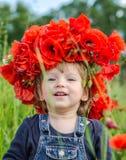 El jugar del bebé de la niña feliz en el campo de la amapola con una guirnalda, un ramo de amapolas rojas del color A y las marga Imágenes de archivo libres de regalías