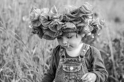 El jugar del bebé de la niña feliz en el campo de la amapola con una guirnalda, un ramo de amapolas rojas del color A y las marga Fotografía de archivo