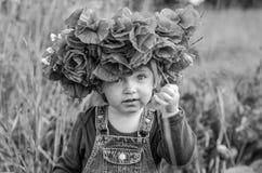 El jugar del bebé de la niña feliz en el campo de la amapola con una guirnalda, un ramo de amapolas rojas del color A y las marga Imagenes de archivo