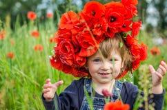El jugar del bebé de la niña feliz en el campo de la amapola con una guirnalda, un ramo de amapolas rojas del color A y las marga Imagen de archivo libre de regalías