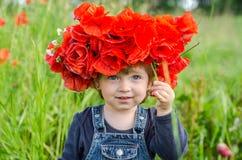 El jugar del bebé de la niña feliz en el campo de la amapola con una guirnalda, un ramo de amapolas rojas del color A y las marga Fotos de archivo libres de regalías