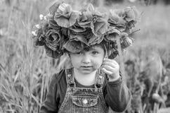 El jugar del bebé de la niña feliz en el campo de la amapola con una guirnalda, un ramo de amapolas rojas del color A y las marga Fotografía de archivo libre de regalías