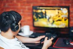 El jugar del hombre juegos de ordenador en auriculares y consola imagen de archivo