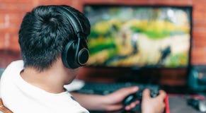 El jugar del hombre juegos de ordenador en auriculares y consola fotografía de archivo