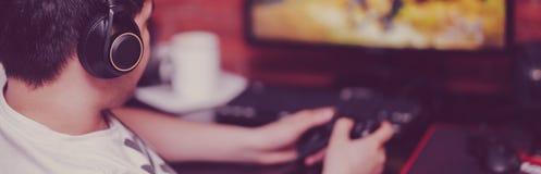 El jugar del hombre juegos de ordenador en auriculares y consola imagenes de archivo