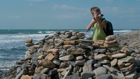 El jugar del muchacho, ocultando detrás de una fortaleza de piedras en la playa de la orilla de mar almacen de video