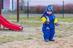 El jugar del niño pequeño al aire libre en patio de la ciudad Fotografía de archivo
