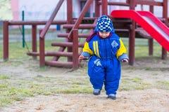 El jugar del niño pequeño al aire libre en patio de la ciudad Foto de archivo libre de regalías