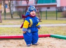 El jugar del niño pequeño al aire libre en patio de la ciudad Imagen de archivo