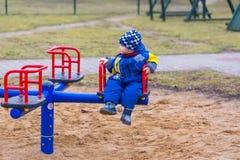 El jugar del niño pequeño al aire libre en patio de la ciudad Foto de archivo