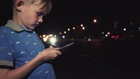 El jugar del niño pequeño del teléfono móvil en ciudad en la noche