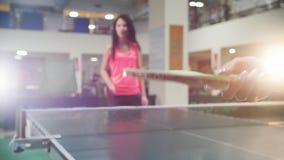 El jugar del ping-pong La mujer joven bate una bola con una pequeña estafa almacen de video