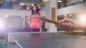El jugar del ping-pong La mujer joven bate una bola con una pequeña estafa para los tenis de mesa almacen de video