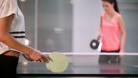 El jugar del ping-pong Los turnos de la mujer joven la bola, su opositor fallan y la mujer coge la bola con una mano metrajes