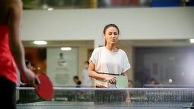 El jugar del ping-pong Mujer sonriente joven que juega a tenis de mesa La mujer falta la bola y va a cogerla  metrajes