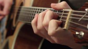 El jugar en la guitarra acústica Instrumento musical con las manos del guitarrista almacen de metraje de vídeo