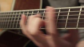 El jugar en la guitarra acústica Instrumento musical con las manos del guitarrista almacen de video