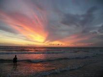 El jugar en la playa en la puesta del sol Imagenes de archivo
