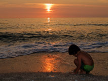 El jugar en la playa en la puesta del sol Fotografía de archivo