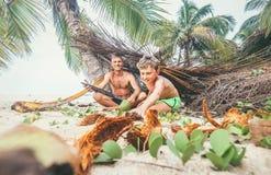 El jugar en Robinzones: el padre y el hijo construyeron una choza de la palmera Fotos de archivo