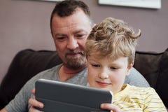 El jugar en una tableta de Digitaces con el papá Imagenes de archivo