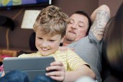 El jugar en una tableta de Digitaces con el papá Imagen de archivo libre de regalías