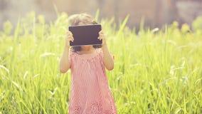 El jugar feliz de la muchacha al aire libre con la tableta Fotografía de archivo