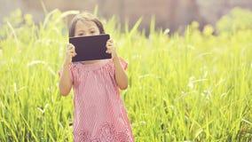 El jugar feliz de la muchacha al aire libre con la tableta Fotos de archivo