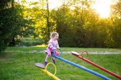 El jugar feliz de la niña, yendo para arriba anuncio abajo en una oscilación Foto de archivo