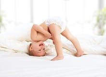 El jugar feliz del niño del bebé   en cama Imagen de archivo