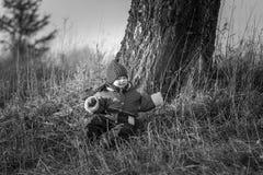 El jugar feliz joven del muchacho al aire libre y el sentarse debajo de árbol viejo Imagenes de archivo