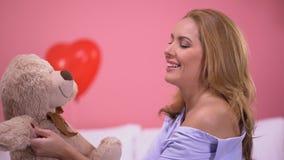 El jugar femenino hermoso con el oso de peluche que se sienta en el dormitorio, regalo precioso, amor almacen de video